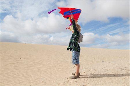 Boy flying kite on beach Stock Photo - Premium Royalty-Free, Code: 649-05820302
