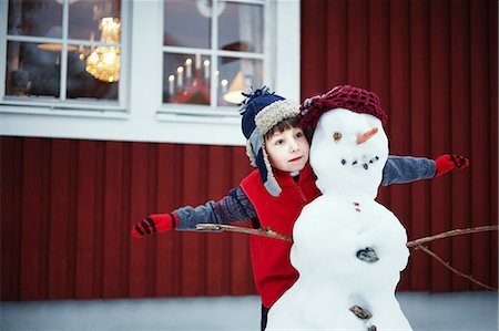 flying - Boy playing with snowman outdoors Stock Photo - Premium Royalty-Free, Code: 649-05820495