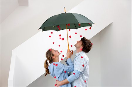 people with umbrellas in the rain - Couple standing under shower of hearts Stock Photo - Premium Royalty-Free, Code: 649-05820552