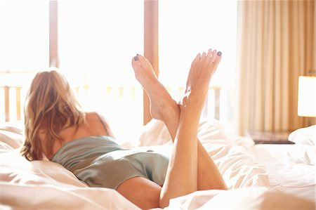Woman laying on bed Stock Photo - Premium Royalty-Free, Code: 649-05821082