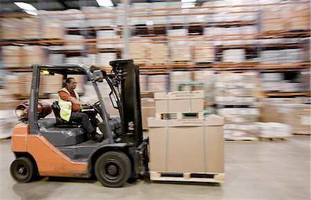 Blurred view of worker in warehouse Stock Photo - Premium Royalty-Free, Code: 649-05821219