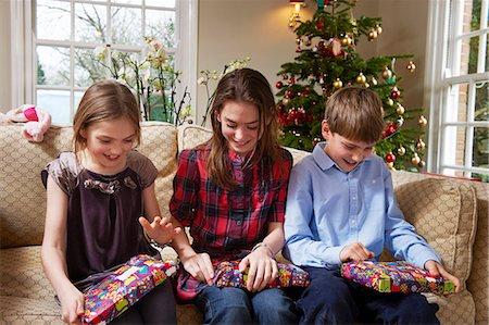 Children opening Christmas gifts Stock Photo - Premium Royalty-Free, Code: 649-05949521