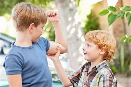 Boy feeling brothers biceps outdoors Stock Photo - Premium Royalty-Free, Code: 649-05949581