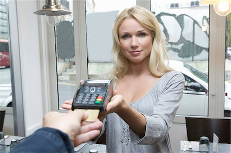 Hostess offering credit card machine Stock Photo - Premium Royalty-Free, Code: 649-05949606