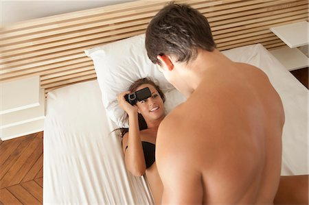 desire - Woman taking video of boyfriend in bed Stock Photo - Premium Royalty-Free, Code: 649-05949646