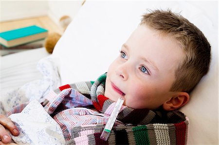 Boy with thermometer in mouth in bed Stock Photo - Premium Royalty-Free, Code: 649-05949800