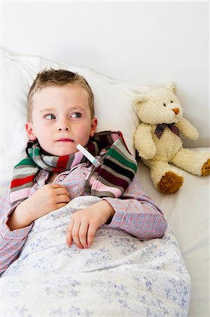 Boy with thermometer in mouth in bed Stock Photo - Premium Royalty-Free, Code: 649-05949801