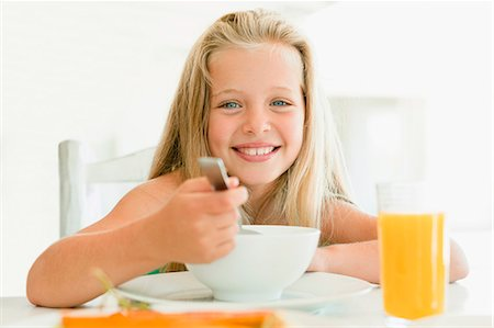 Girl eating cereal at breakfast table Stock Photo - Premium Royalty-Free, Code: 649-05949952