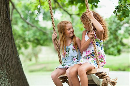 Smiling girls sitting in tree swing Stock Photo - Premium Royalty-Free, Code: 649-05950114