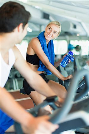flirting - Couple using exercise machines in gym Stock Photo - Premium Royalty-Free, Code: 649-05950201