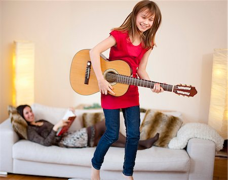 Girl playing guitar in living room Stock Photo - Premium Royalty-Free, Code: 649-05950575