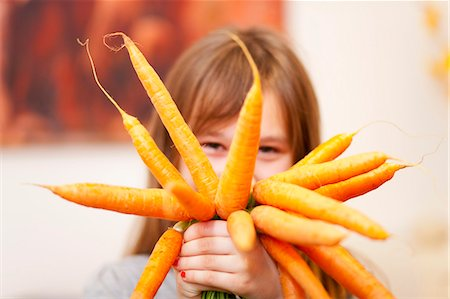 Smiling girl holding bunch of carrots Stock Photo - Premium Royalty-Free, Code: 649-05950572