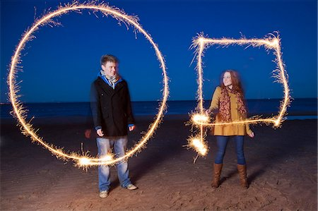 Couple playing with sparklers on beach Stock Photo - Premium Royalty-Free, Code: 649-05950696