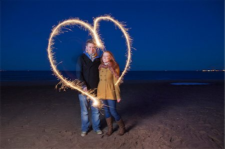 Couple playing with sparklers on beach Stock Photo - Premium Royalty-Free, Code: 649-05950698