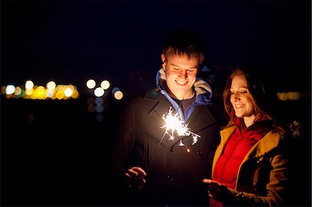 Smiling couple playing with sparklers Stock Photo - Premium Royalty-Free, Code: 649-05950705