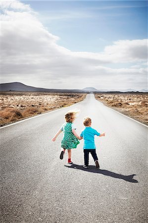 Children walking on paved rural road Stock Photo - Premium Royalty-Free, Code: 649-05950799