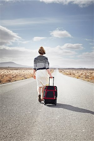 Woman rolling luggage on rural road Stock Photo - Premium Royalty-Free, Code: 649-05950791