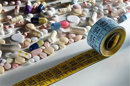 Scattered pills and measuring tape Stock Photo - Premium Royalty-Free, Code: 649-05951259