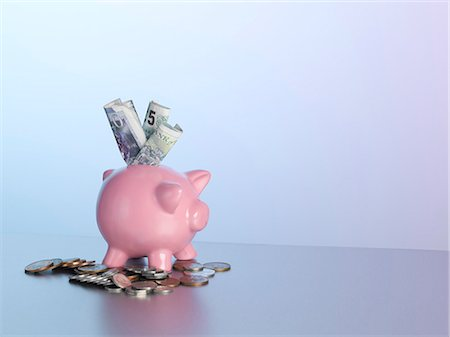 Piggy bank with money on table Stock Photo - Premium Royalty-Free, Code: 649-06000336