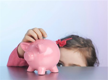 reaching - Girl putting coin in piggy bank Stock Photo - Premium Royalty-Free, Code: 649-06000341