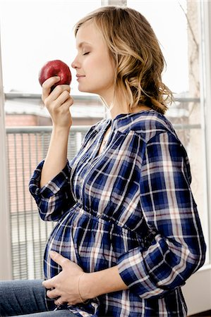 portrait of pregnant woman - Smiling pregnant woman smelling apple Stock Photo - Premium Royalty-Free, Code: 649-06000424