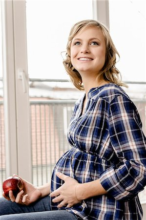 portrait of pregnant woman - Smiling pregnant woman eating apple Stock Photo - Premium Royalty-Free, Code: 649-06000423