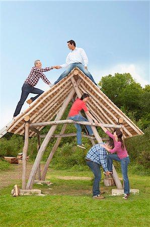People climbing log hut outdoors Stock Photo - Premium Royalty-Free, Code: 649-06000599