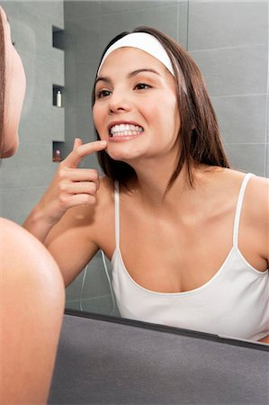 Woman examining her teeth in mirror Stock Photo - Premium Royalty-Free, Code: 649-06000646