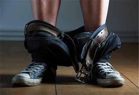 Mans jeans fallen around his ankles Stock Photo - Premium Royalty-Free, Code: 649-06000727