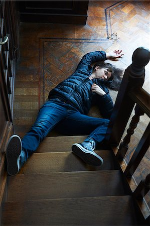 dead woman - Teenage boy laying at foot of stairs Stock Photo - Premium Royalty-Free, Code: 649-06000732
