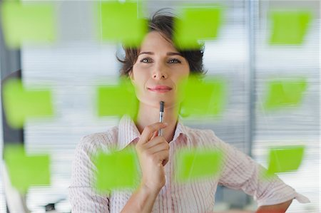 Businesswoman reading sticky notes Stock Photo - Premium Royalty-Free, Code: 649-06000838
