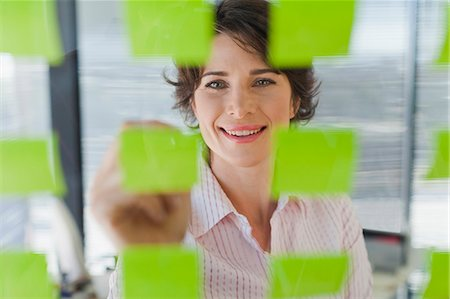 Businesswoman writing on sticky notes Stock Photo - Premium Royalty-Free, Code: 649-06000839