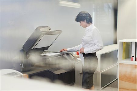 Businesswoman making copies in office Stock Photo - Premium Royalty-Free, Code: 649-06000949