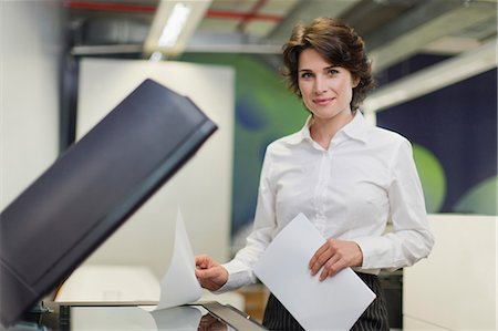 Businesswoman making copies in office Stock Photo - Premium Royalty-Free, Code: 649-06000950