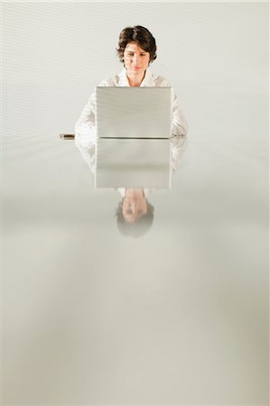Businesswoman reflected in table Stock Photo - Premium Royalty-Free, Code: 649-06000965
