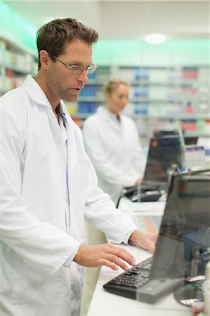 supply - Pharmacist using computer at counter Stock Photo - Premium Royalty-Free, Code: 649-06001039