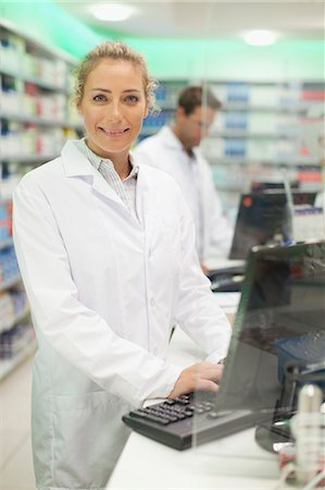 Pharmacist using computer at counter Stock Photo - Premium Royalty-Free, Code: 649-06001042