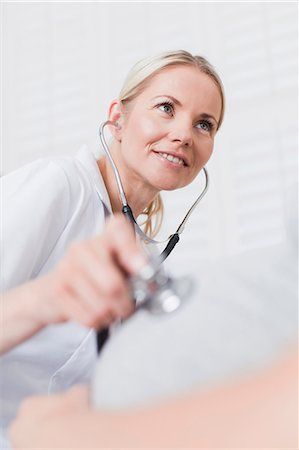 Doctor examining pregnant womans belly Stock Photo - Premium Royalty-Free, Code: 649-06001069