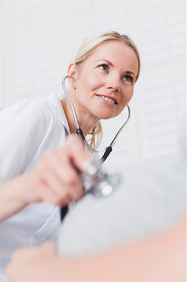 Doctor examining pregnant womans belly Stock Photo - Premium Royalty-Free, Image code: 649-06001069