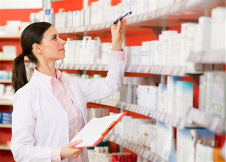 Pharmacist browsing medicine on shelves Stock Photo - Premium Royalty-Free, Code: 649-06001326