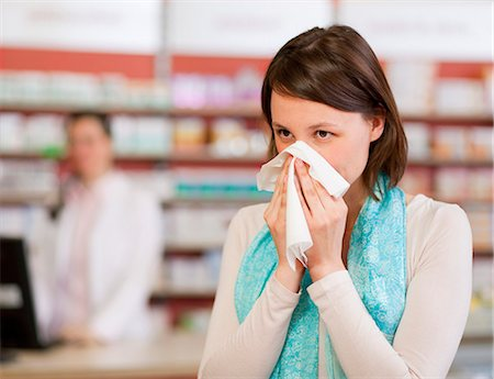 people coughing or sneezing - Woman blowing nose in pharmacy Stock Photo - Premium Royalty-Free, Code: 649-06001336