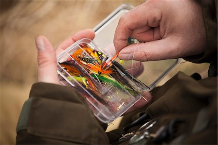 Man pulling fishing tackle from box Stock Photo - Premium Royalty-Free, Code: 649-06001370