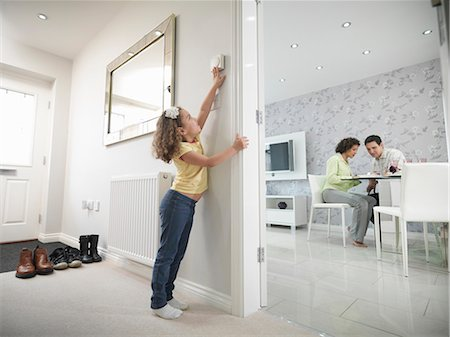 Girl reaching for thermostat Stock Photo - Premium Royalty-Free, Code: 649-06001529