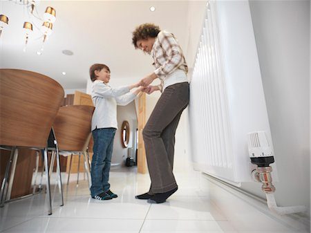 Mother and son holding hands in kitchen Stock Photo - Premium Royalty-Free, Code: 649-06001545