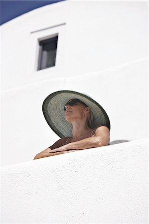 santorini - Woman in sunhat standing on balcony Stock Photo - Premium Royalty-Free, Code: 649-06001695