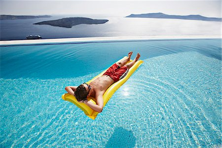 Teenage boy relaxing on raft in pool Stock Photo - Premium Royalty-Free, Code: 649-06001699