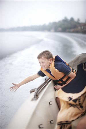Teenage boy reaching to water from boat Stock Photo - Premium Royalty-Free, Code: 649-06001711