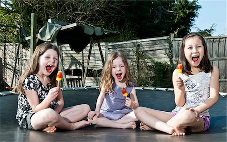 Girls eating popsicles on trampoline Stock Photo - Premium Royalty-Free, Code: 649-06001979