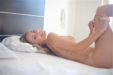 Woman pulling on pantyhose on bed Stock Photo - Premium Royalty-Free, Code: 649-06039972