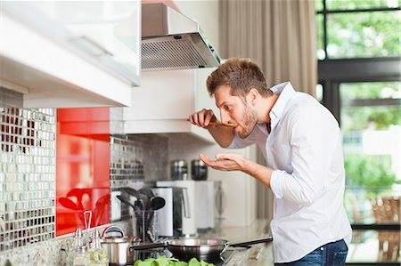 Man tasting food in kitchen Stock Photo - Premium Royalty-Free, Code: 649-06040114